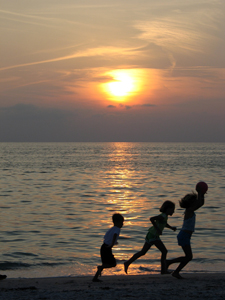 Kids on the beach at sunset